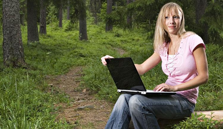 Kvinna som surfar trådlöst i skogen