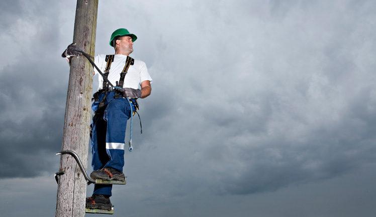 Elnätstekniker högt upp i stolpe blickar ut i skyn